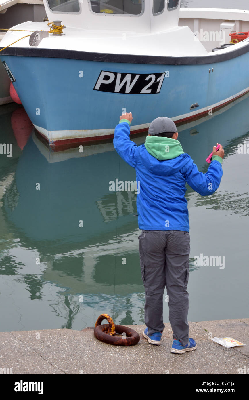 A young boy or child using a han crabbing line to catch crabs standing on a harbour wall at padstow in cornwall - Stock Image