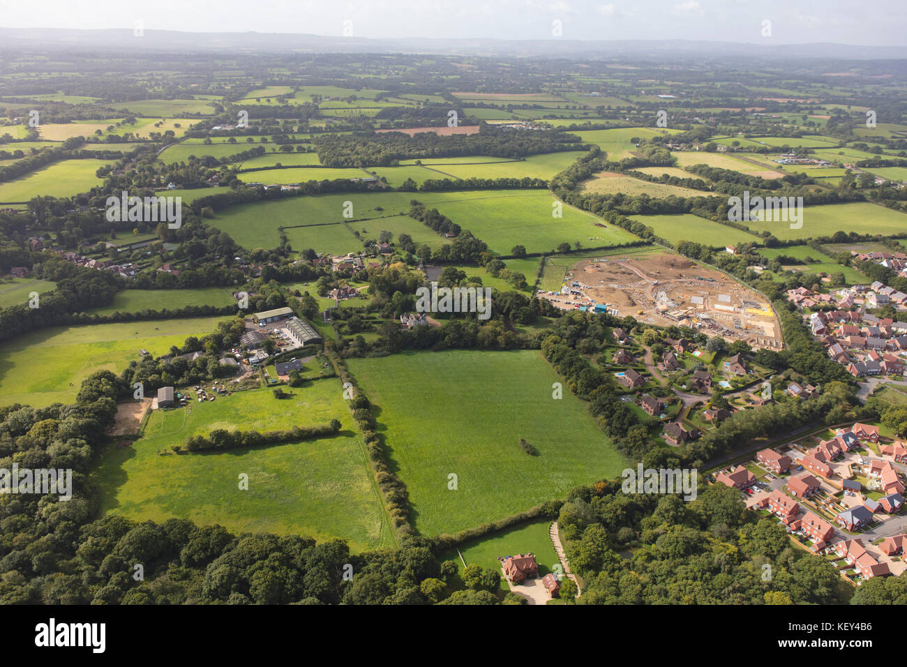 An aerial view illustrating housing development around the edge of a Sussex town - Stock Image