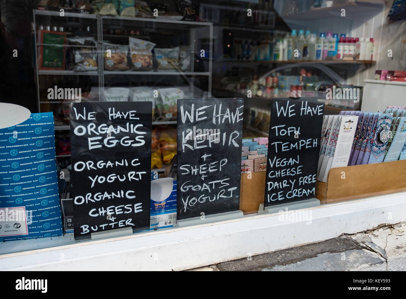 Window display of signs showing organic foods for sale in Deli shop in historic village of Crail in East Neuk of - Stock Image