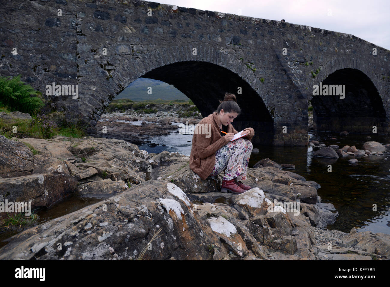 17 year old girl writes in her journal at old stone bridge over River Slichagan  Isle of Skye, Scot - Stock Image