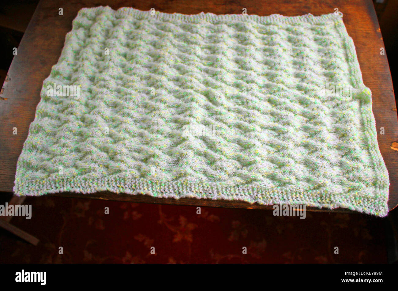 A lovely soft hand knitted baby blanket in colours of pastel shades white, yellow and green. Which has a chevron - Stock Image