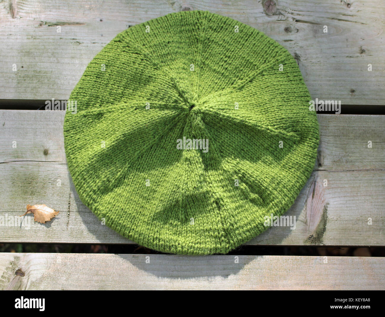 A hand knitted beret on a wooden table. It is a adult sized garment in a sage green shade. - Stock Image