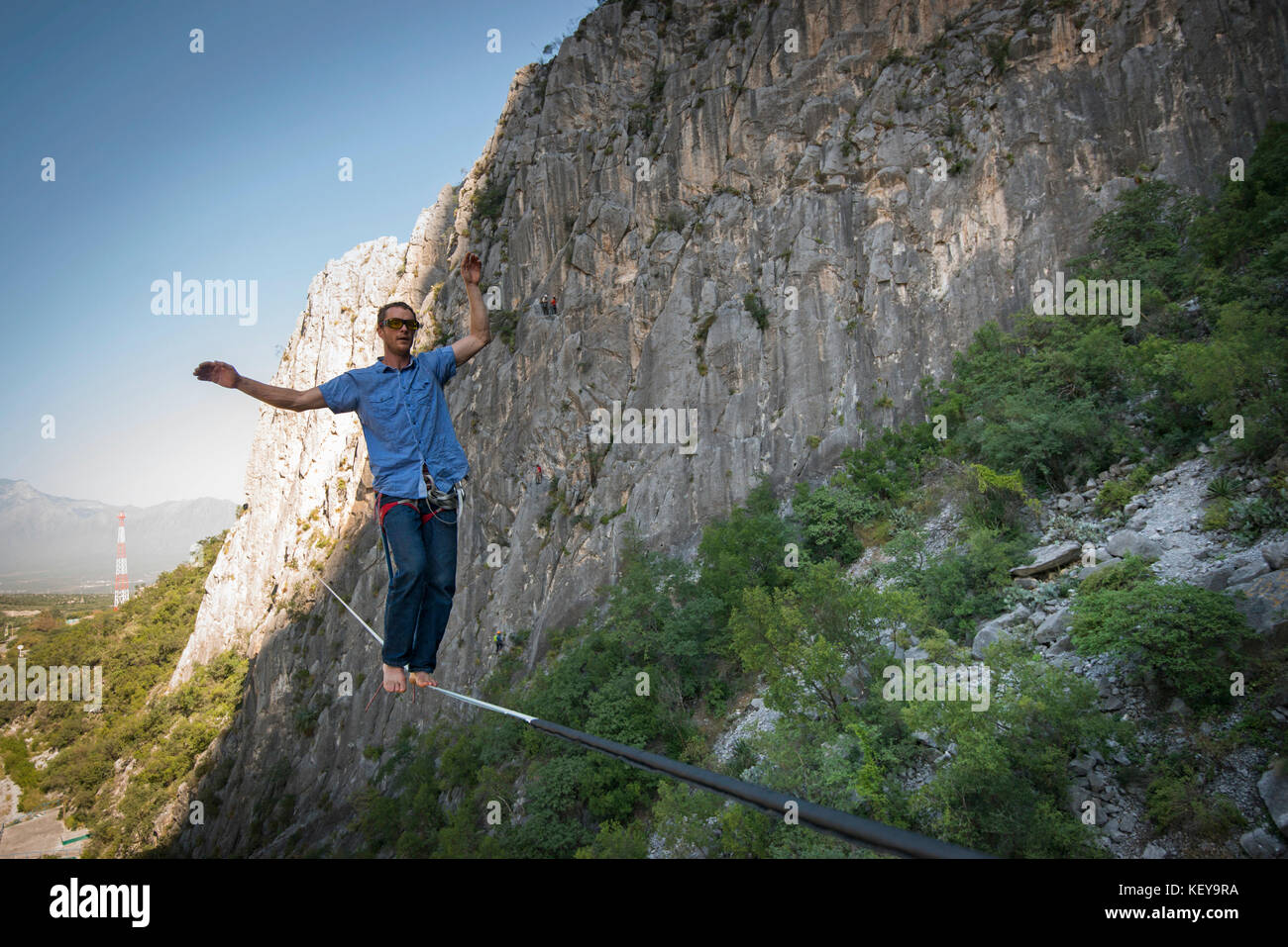 Adventurous man slacklining between two rock walls at El Portero Chico, Monterrey, Mexico Stock Photo