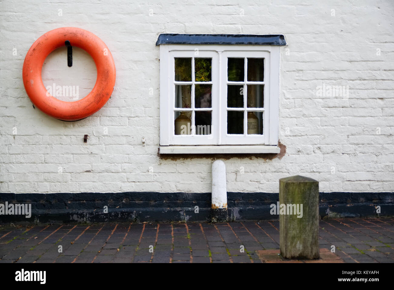Canal side cottage with window and life saving ring on the white wall - Stock Image