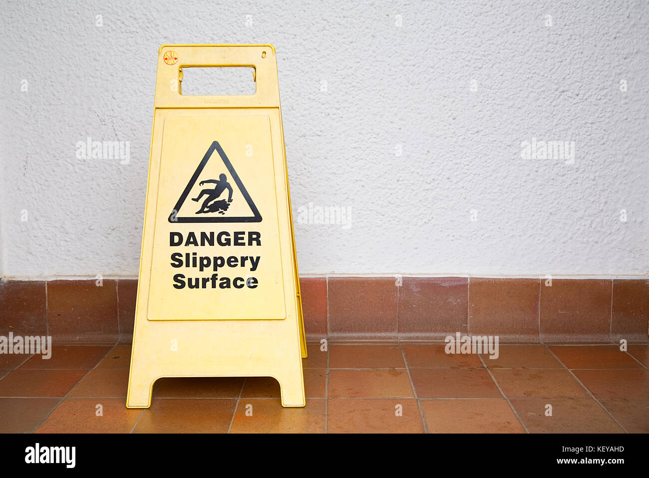 Yellow danger slippery surface sign on tiled floor on the left hand side of the image - Stock Image