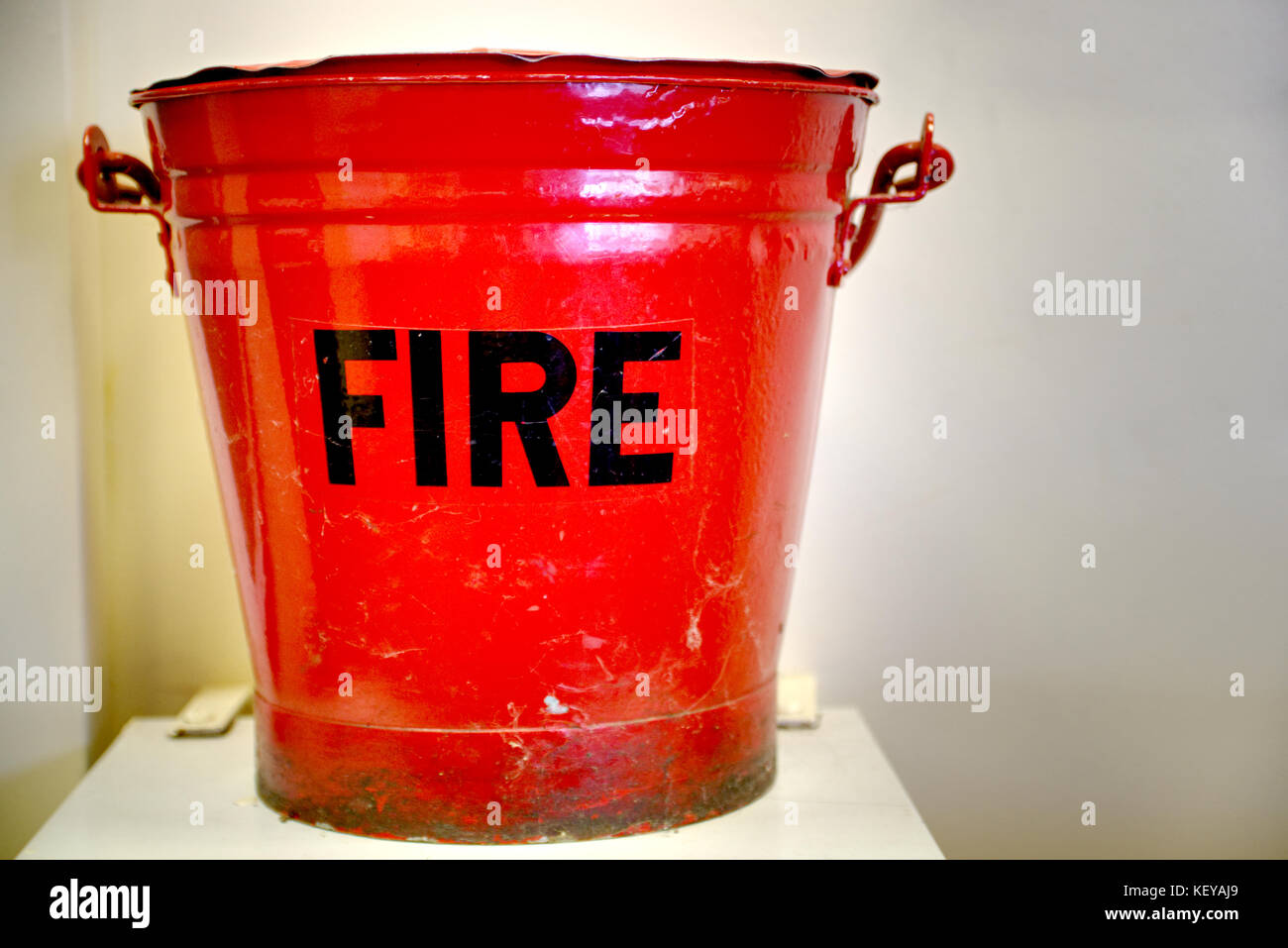 Red fire safety bucket on left hand side of the image - Stock Image