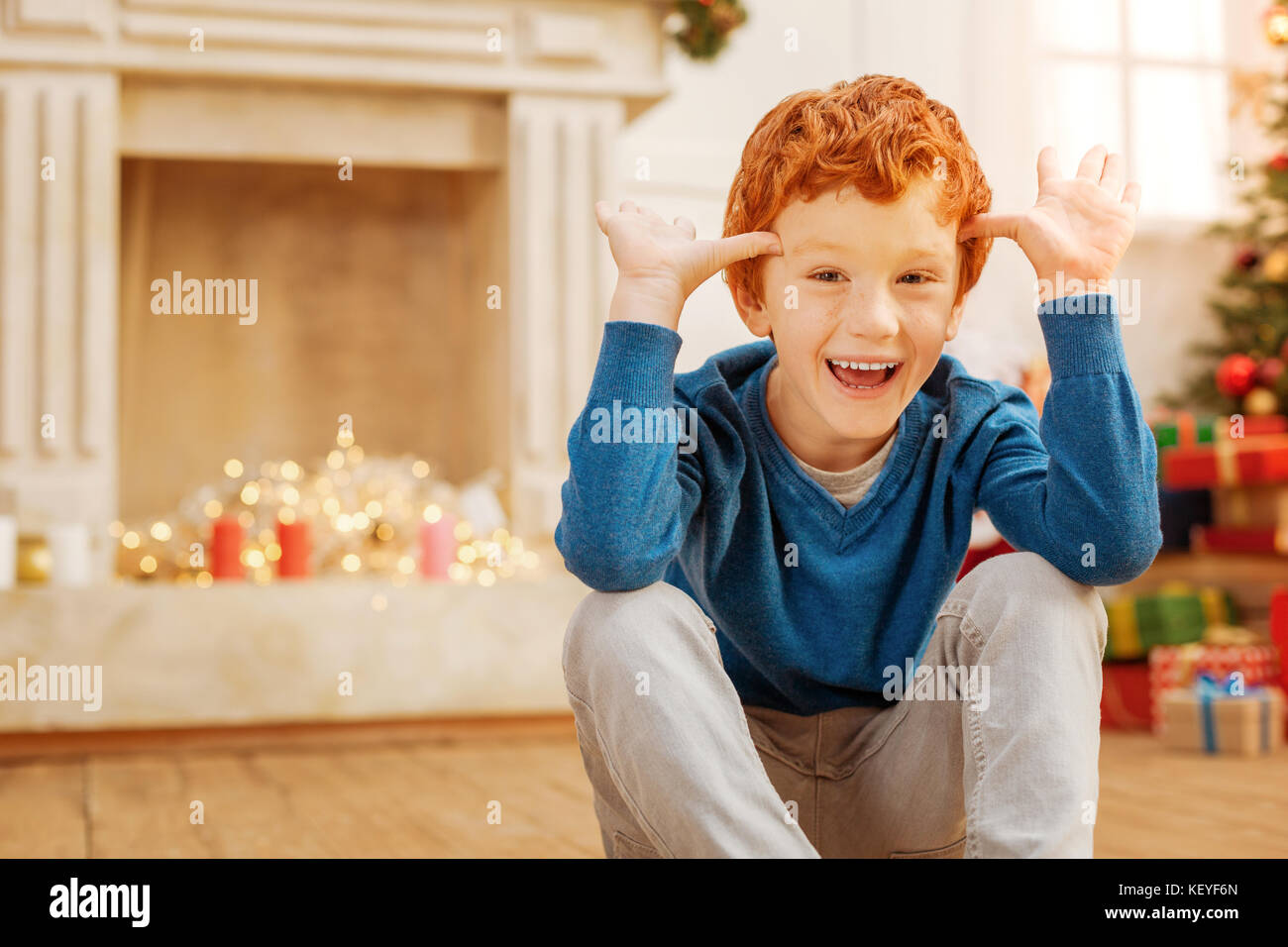 Funny redhead boy making faces while sitting on floor - Stock Image