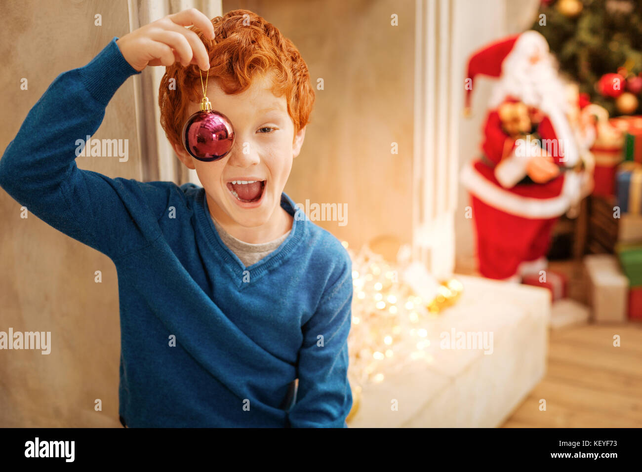Funny redhead boy making funny faces with christmas decorative ball - Stock  Image