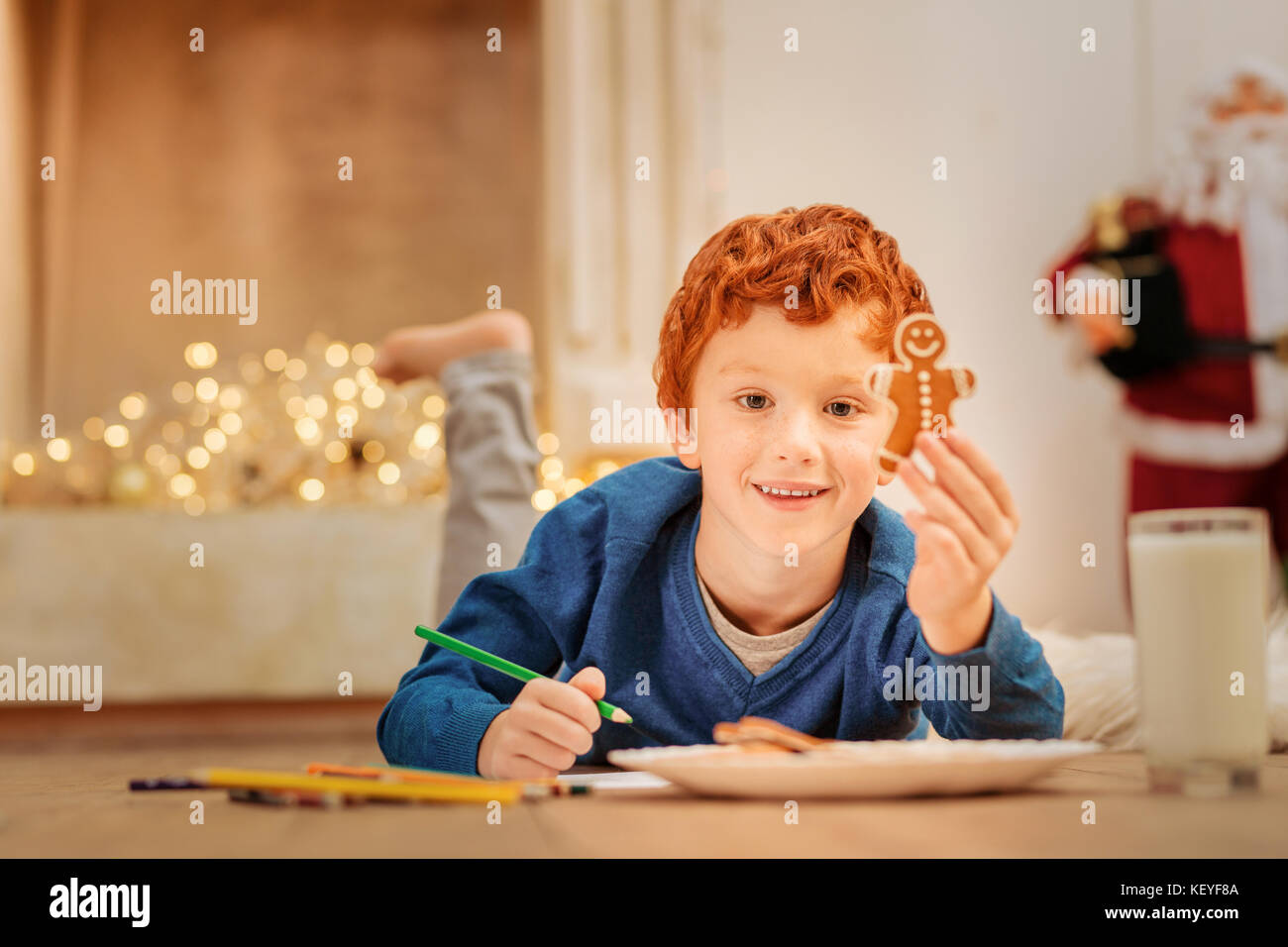 Happy redhead child showing gingerbread man while lying on floor - Stock Image