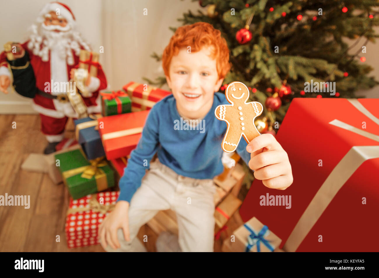 Emotional preteen boy showing gingerbread man into camera - Stock Image