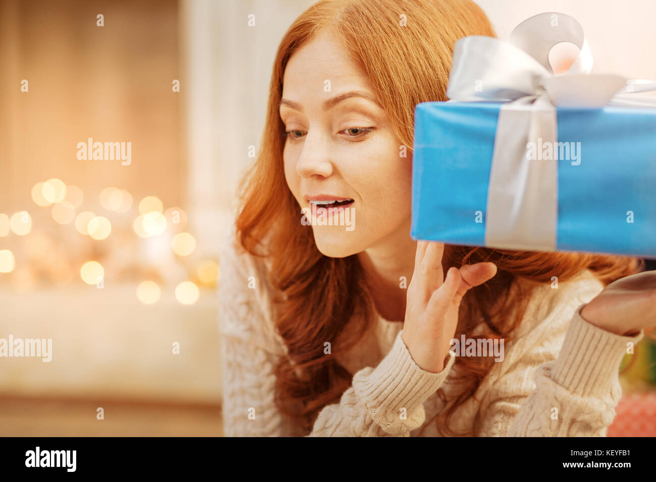 Curious redhead lady guessing what she got for christmas - Stock Image