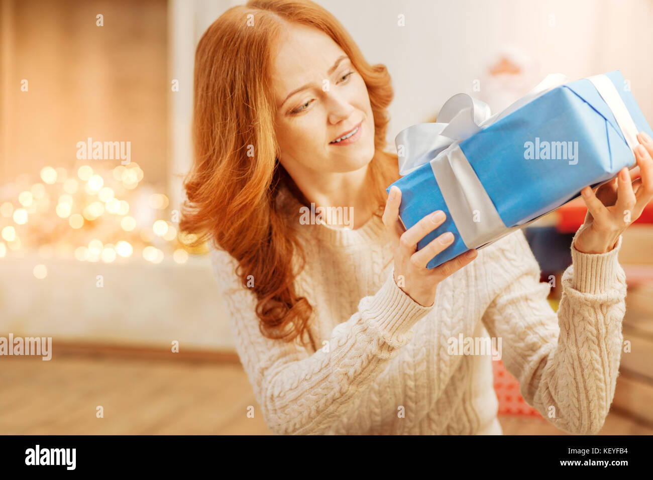 Surprised mature lady looking at christmas present - Stock Image