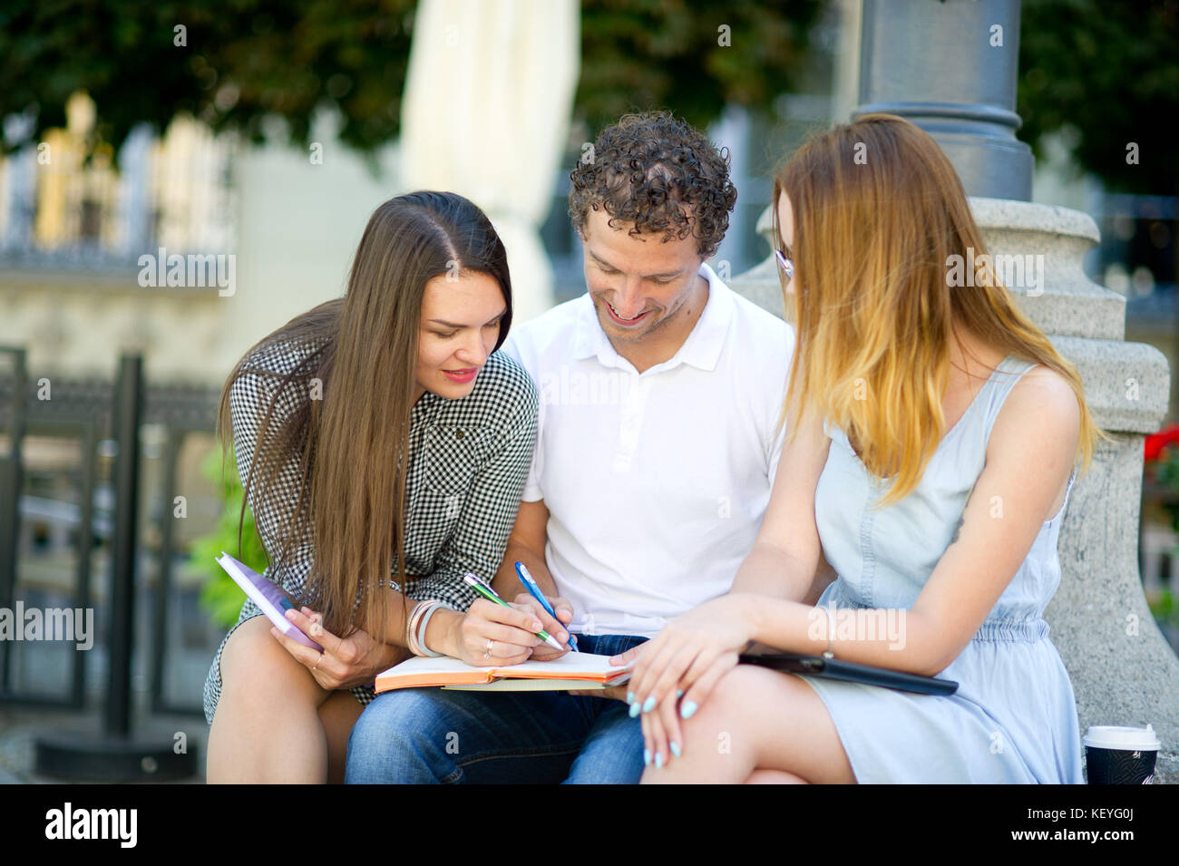 Three students are preparing for exams. Two girls and a guy sitting on a bench and talking animatedly. In the hands - Stock Image