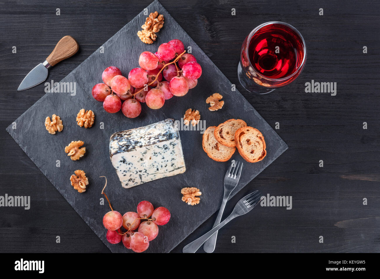 Blue cheese and grapes on black with copy space - Stock Image