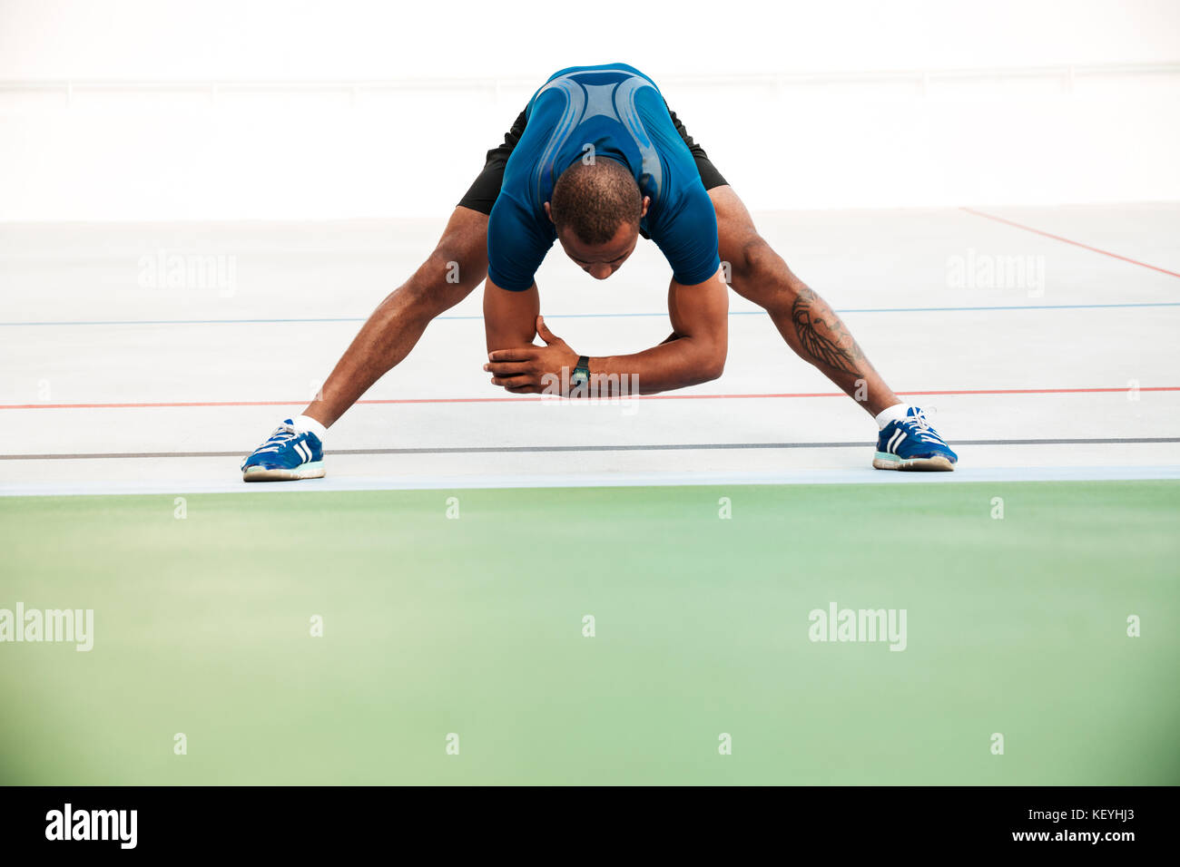 Full length portrait of a young sportsman doing stretching exercises on a track field outdoors - Stock Image