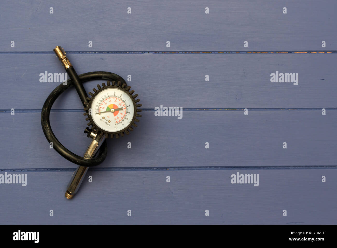 Tyre Inflater with air pressure gauge on blue wooden boards Stock Photo