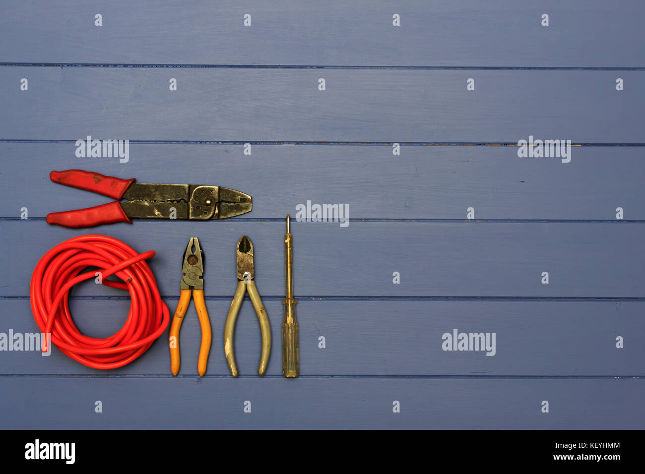 Pair of Pliers, Wire Snips, Small Electrical test screwdriver, pair of wire strippers and roll of red coloured cable - Stock Image