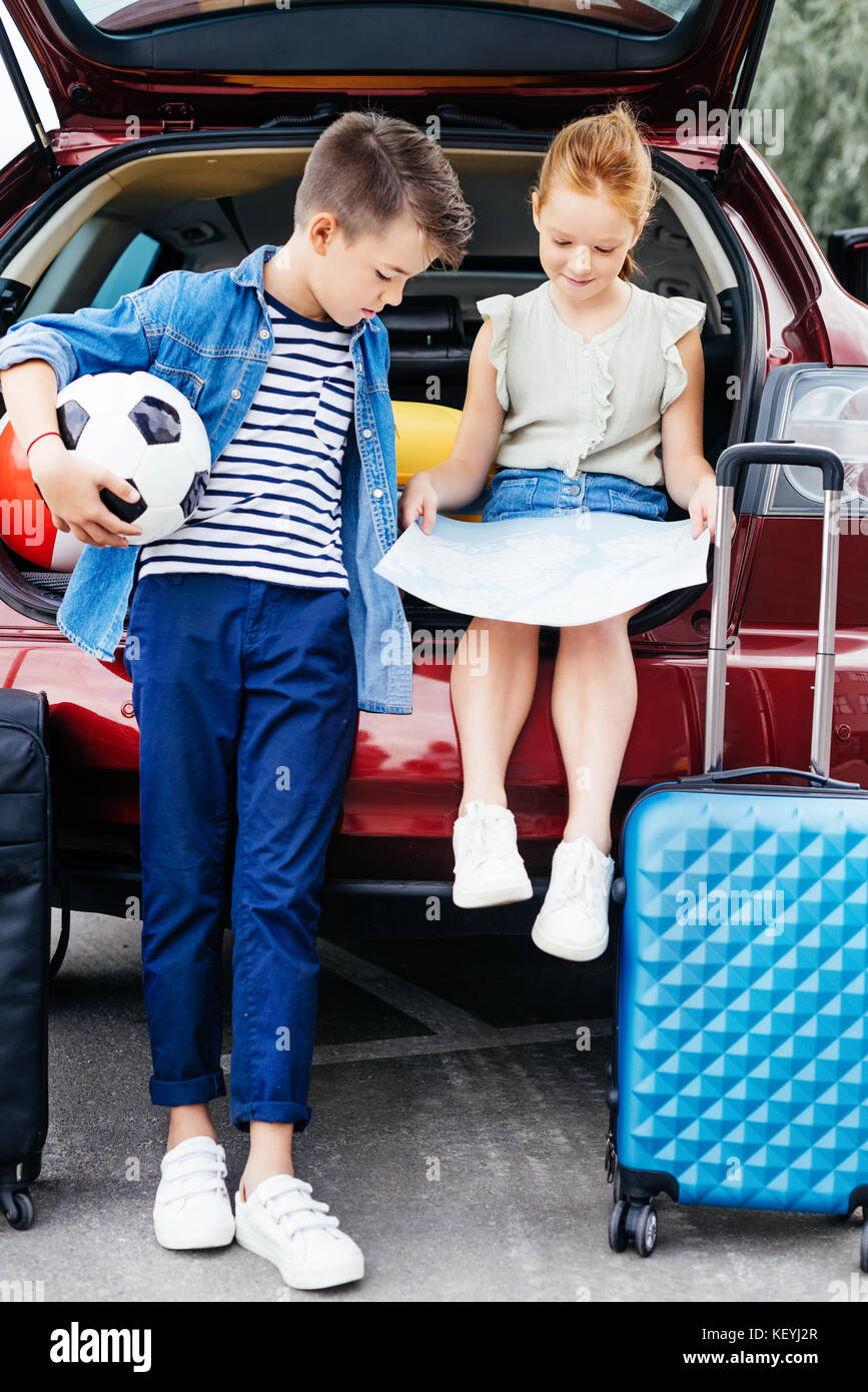 brother and sister in trunk of car - Stock Image