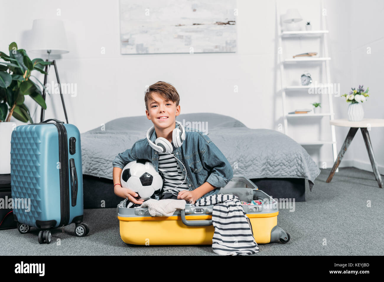 boy sitting in suitcase for trip - Stock Image