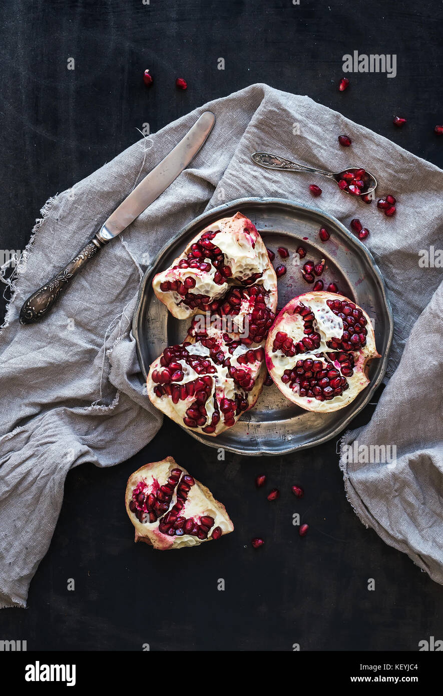 Red ripe peeled pomegranate on rustic metal plate and beige kitchen towel - Stock Image