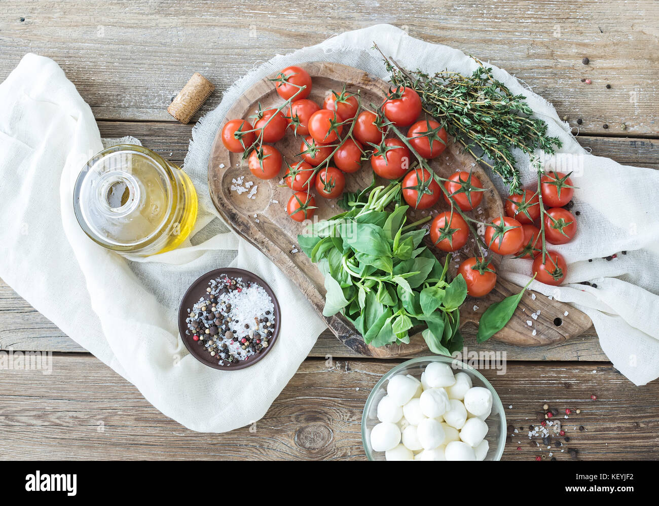 Basil, cherry-tomatoes, mozarella, olive oil, salt, spices on rustic chopping board - Stock Image