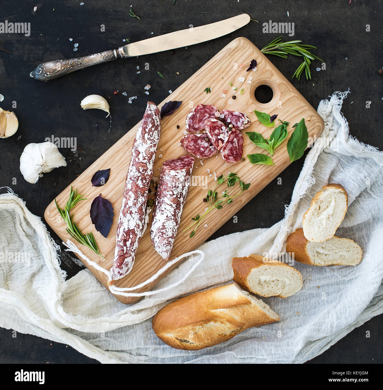 Meat gourmet snack. Salami, garlic, baguette and herbs on rustic wooden board - Stock Image