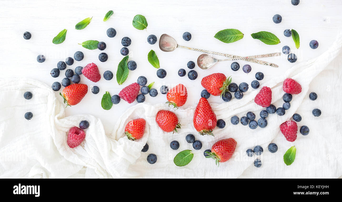 Berry frame with copy space on right. Strawberries, raspberries, blueberries and mint leaves - Stock Image