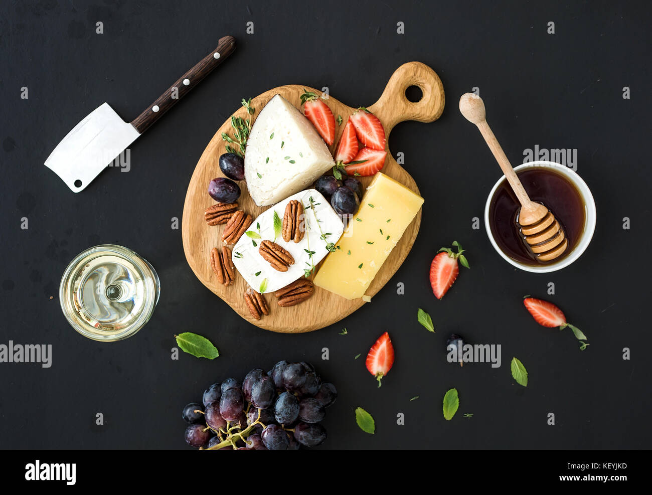 Cheese appetizer selection or whine snack set. Variety of cheese, grapes, pecan nuts, strawberry and honey - Stock Image