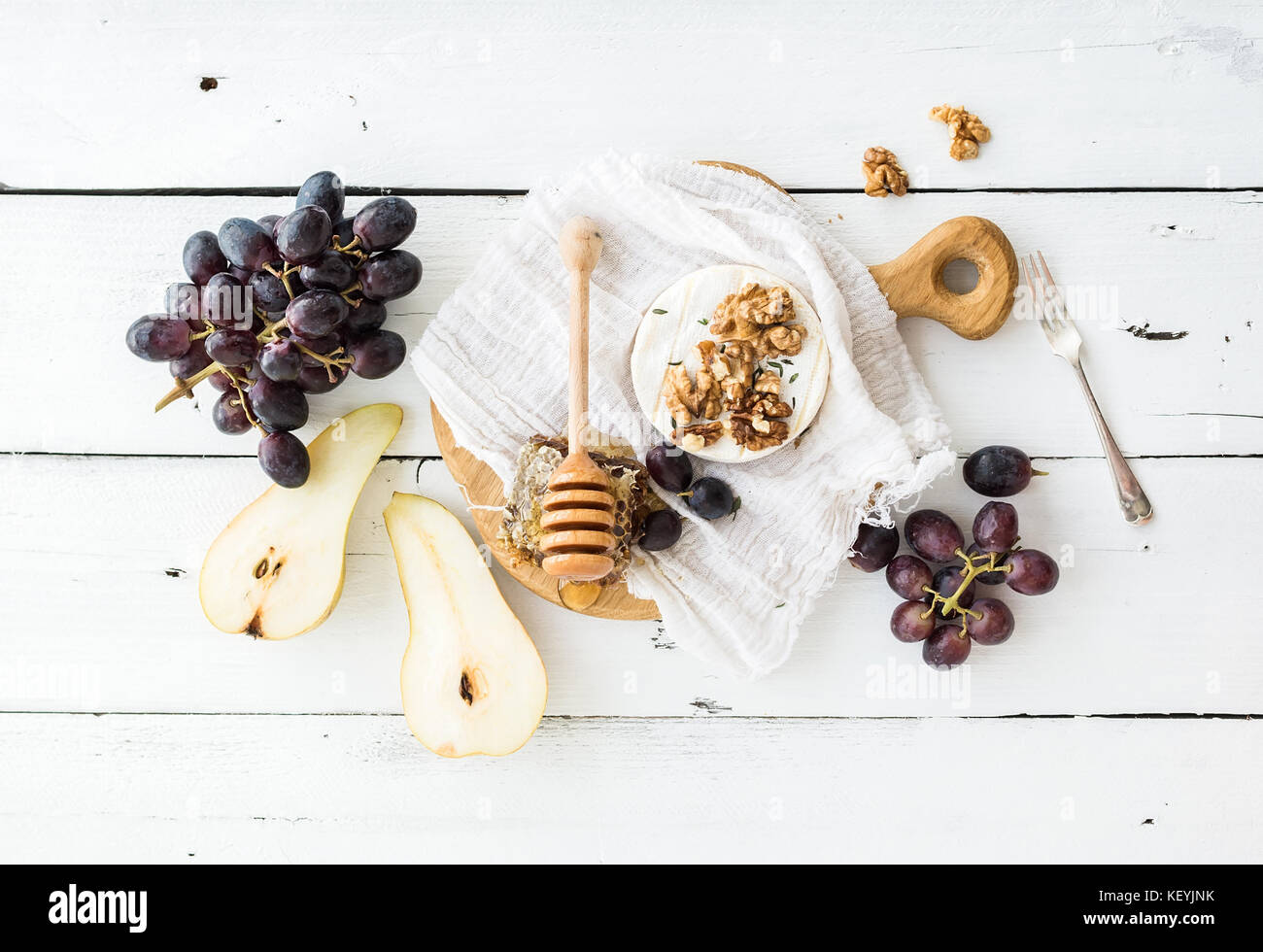 Camembert cheese with grape, walnuts, pear and honey on vintage metal plate - Stock Image