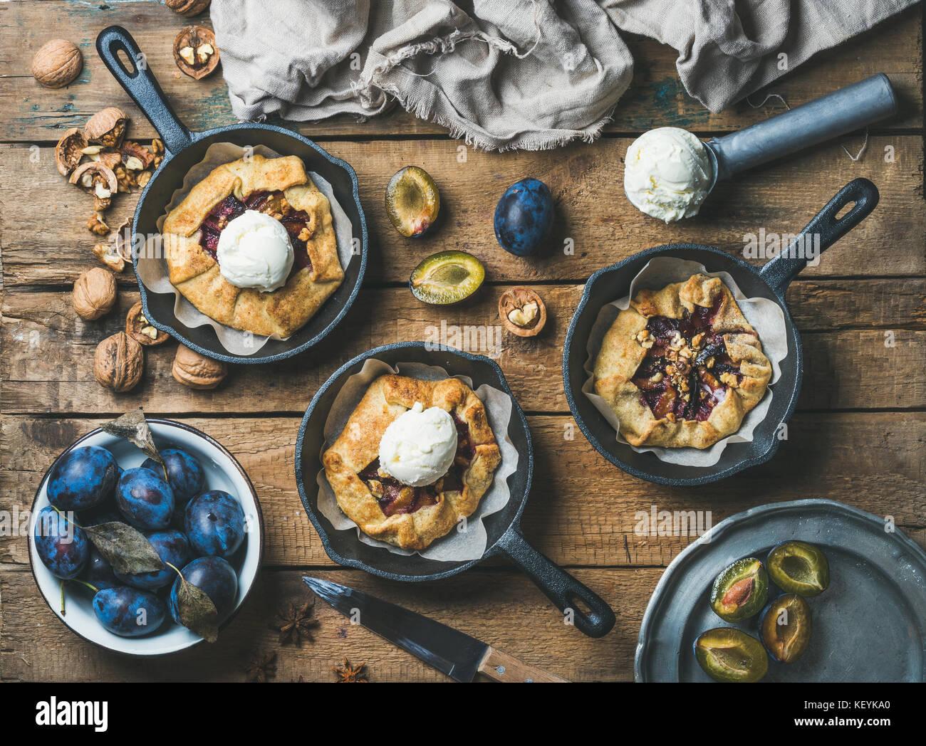 Plum and walnut crostata pie with ice-cream scoops - Stock Image