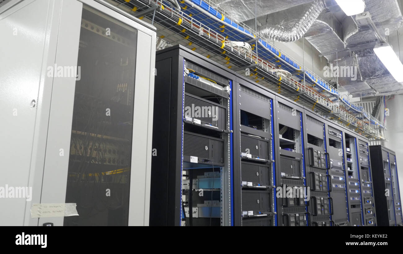 Many powerful servers running in the data center server room. Many servers in a data center. Many racks with servers located in the server room. Bright display a plurality of operating equipment. Stock Photo