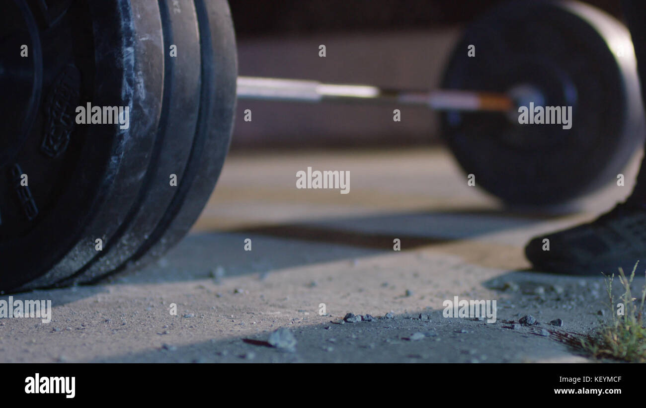 barbell for deadlift and foot athlete powerlifter competitions in powerlifting. Young athlete getting ready for Stock Photo