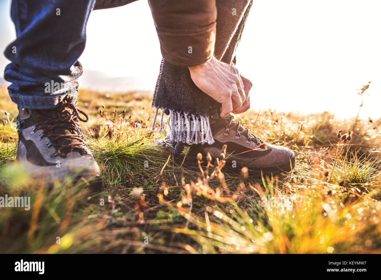 Active senior man on a walk in a beautiful autumn nature. Unrecognizable man tying his shoelaces. Close up. - Stock Image