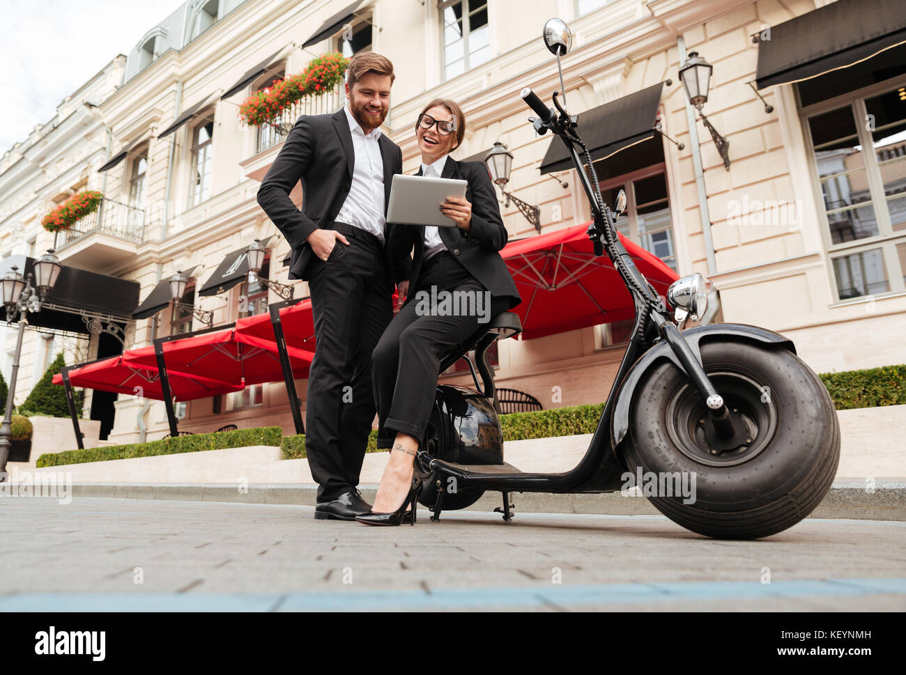 Full length image of happy business couple posing near the modern motorbike outdoors and using talet computer - Stock Image