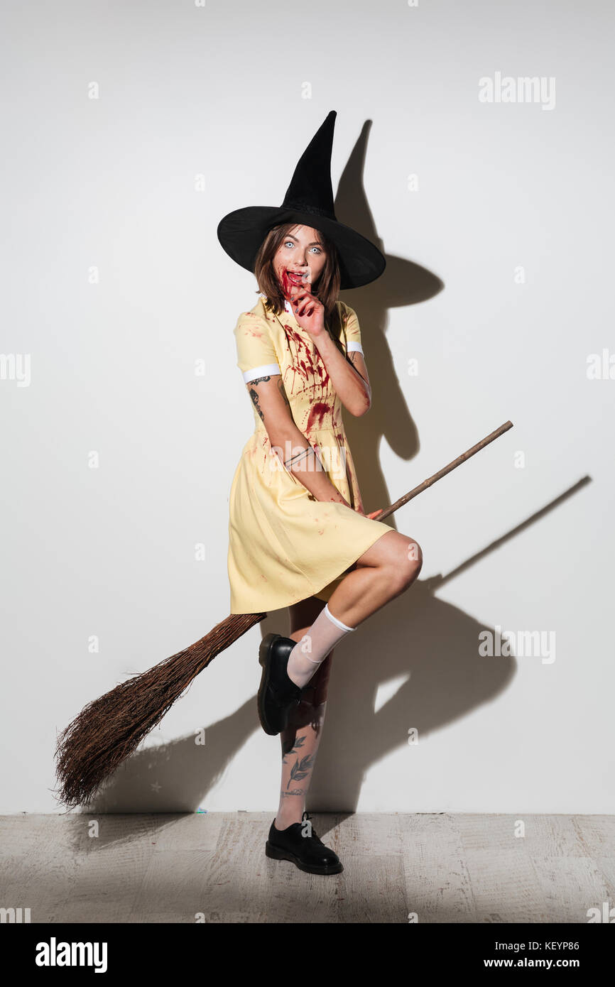 Full length image of smiling crazy woman in halloween costume with open mouth flying on broom like witch and looking at the camera over white backgrou  sc 1 st  Alamy & Full length image of smiling crazy woman in halloween costume with ...