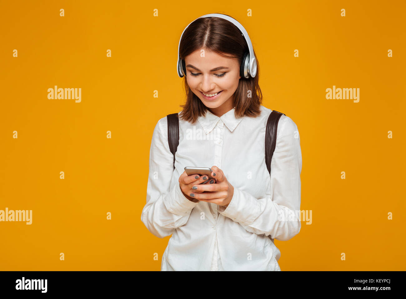 Portrait of a smiling teenage schoolgirl in uniform with headphones holding mobile phone isolated over orange background Stock Photo