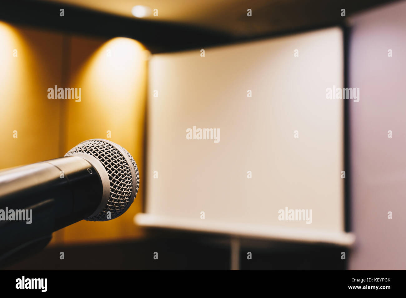 microphone ready to use in the podium and the projector screen on the back of the meeting room for the press conference. - Stock Image