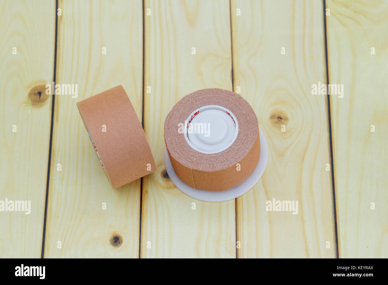 Surgical or medical tape on wooden background - Stock Image