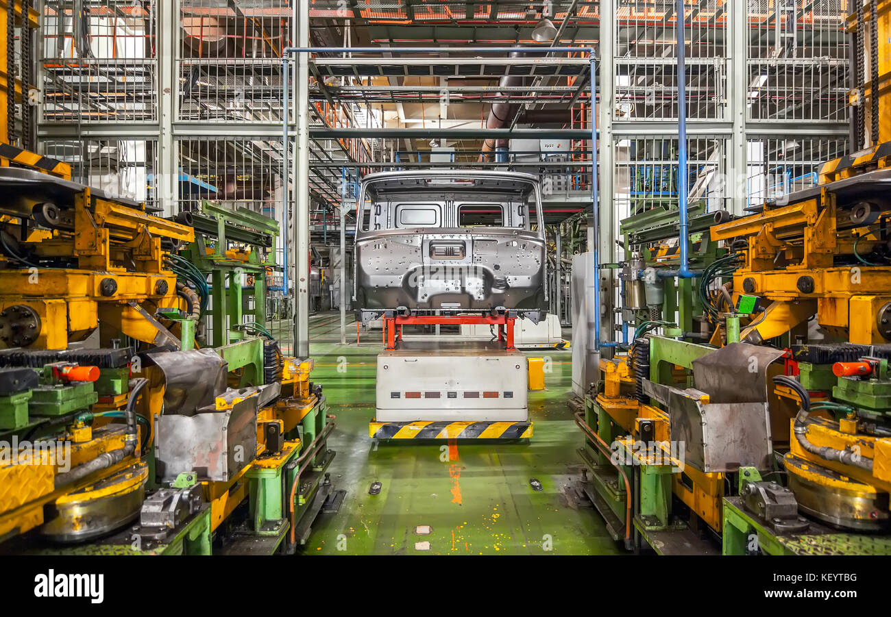 Stopped equipment with car frame at a closed car factory - Stock Image