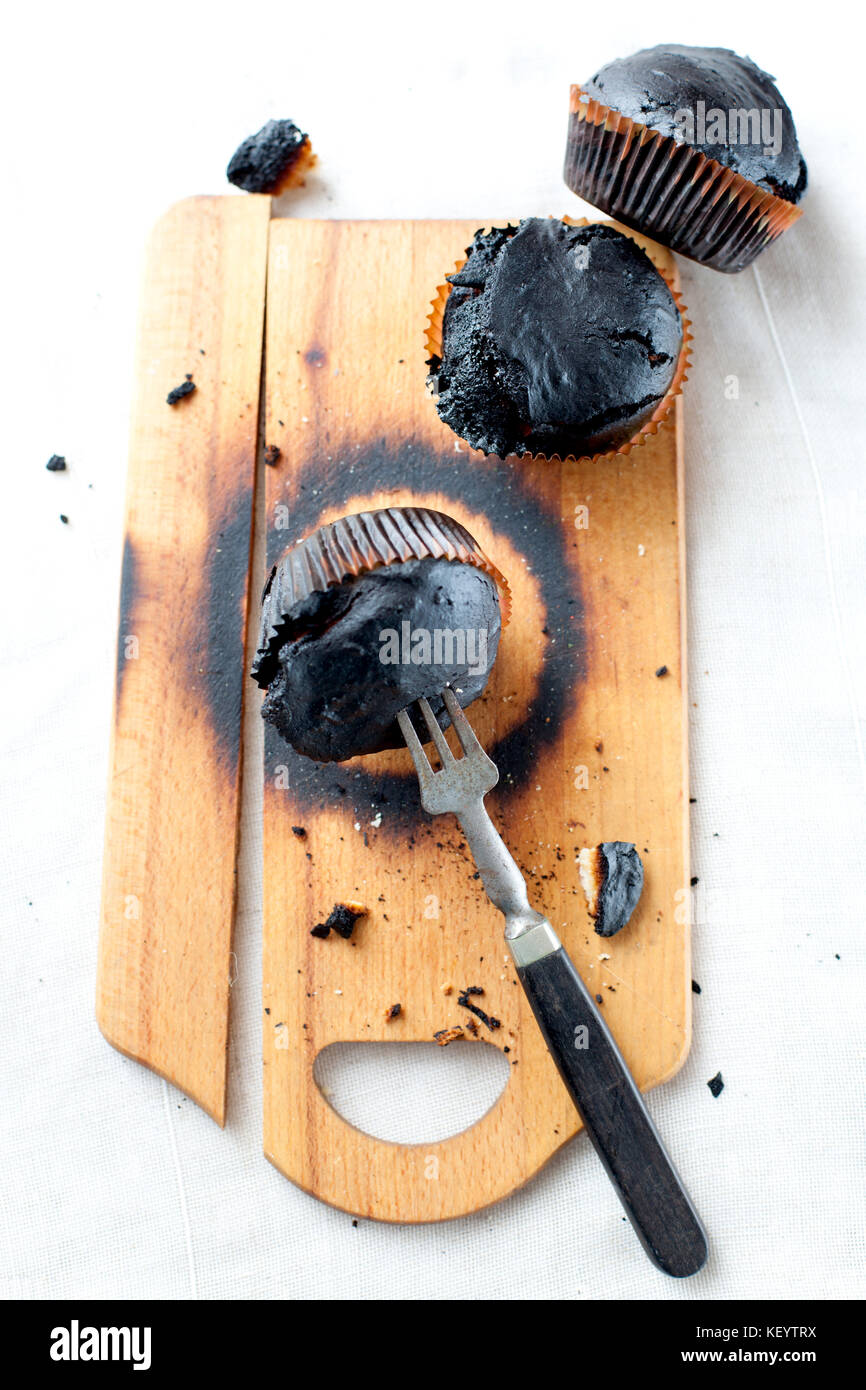 burned muffins - black cupcakes, failed baking, catastrophe in the kitchen, burned on charcoal - Stock Image