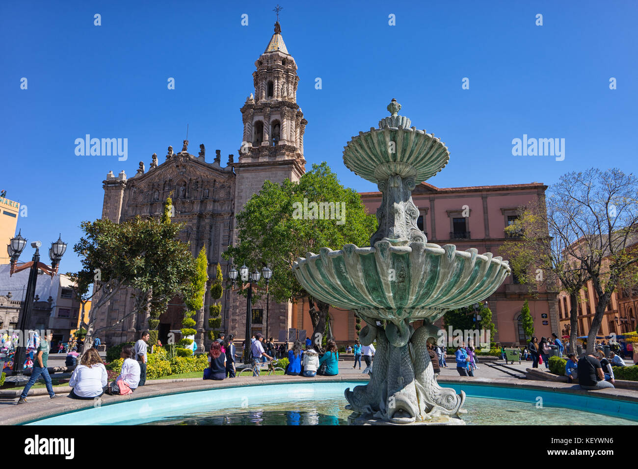 January 18, 2016 San Luis Potosi, Mexico: people sitting on rim of water fountain in front of San Luis cathedral - Stock Image