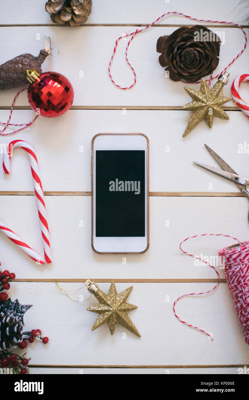 Mobile phone on wooden background with Christmas gifts. Xmas and Happy New Year composition. Flat lay, top view Stock Photo