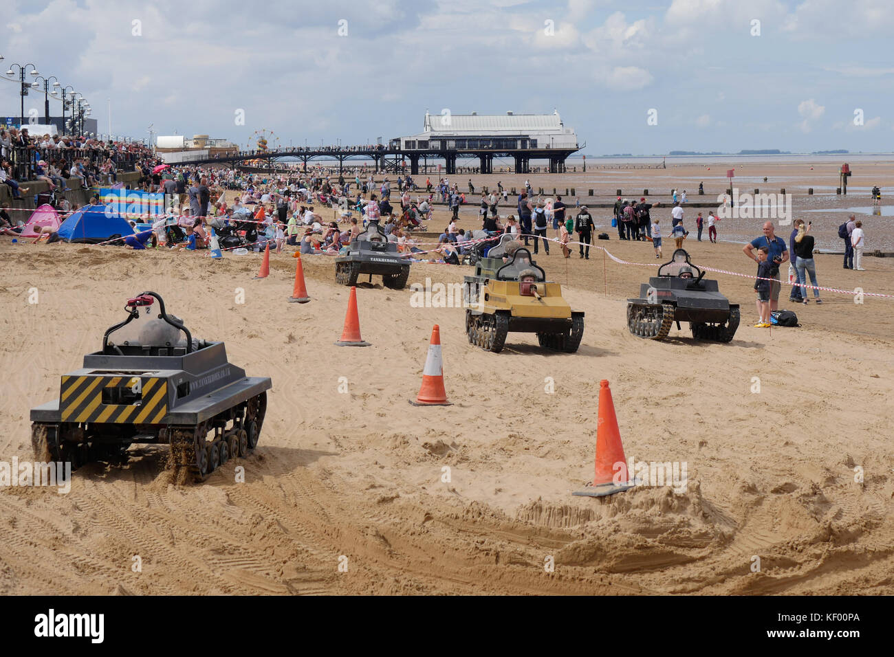 Children play in miniature model tanks on the beach at The