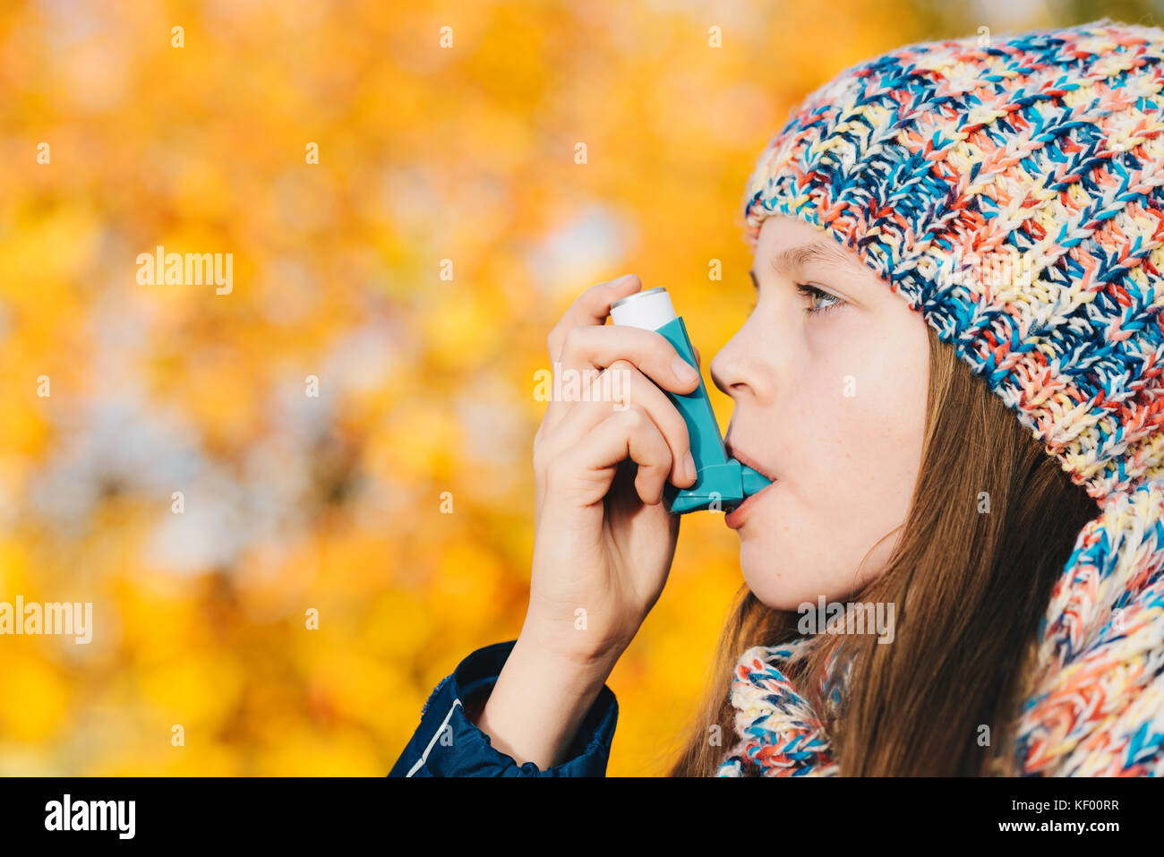 Asthma patient girl inhaling medication for treating shortness of breath and wheezing in a park. Chronic disease - Stock Image