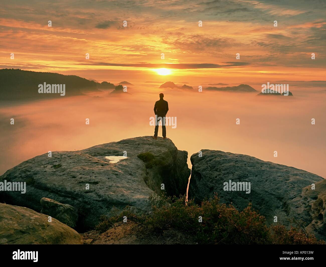 Man stands alone on the peak of rock. Hiker watching to autumn  Sun at horizon . Beautiful moment the miracle of - Stock Image