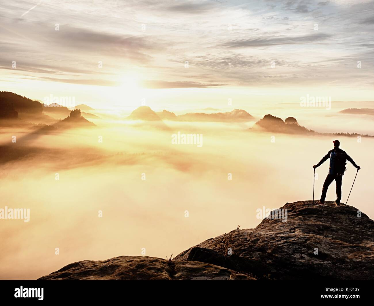Man silhouette with poles in hand. Sunny spring daybreak and tourist guide stay on sharp cliff of mountain. Hiker - Stock Image