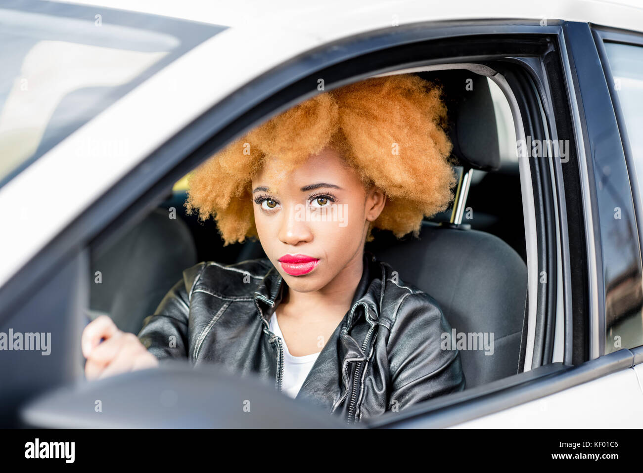 Portrait of a beautiful african woman in the car - Stock Image