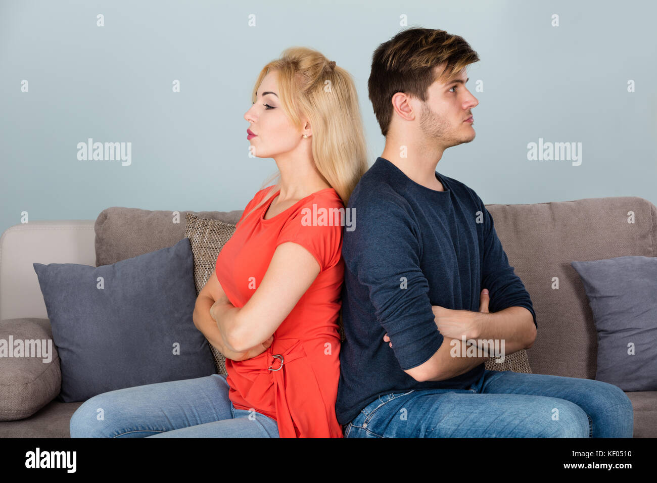 Young Sad Divorcing Couple With Arms Crossed Sitting On Sofa After Quarrel At Home - Stock Image