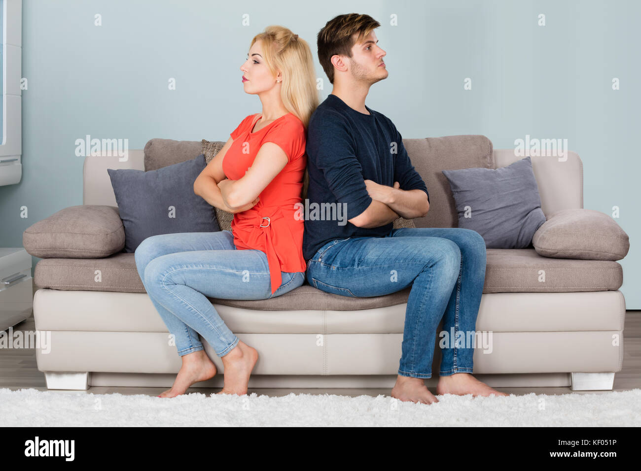 Young Sad Couple In Fight With Arms Crossed Sitting On Sofa After Quarrel At Home - Stock Image