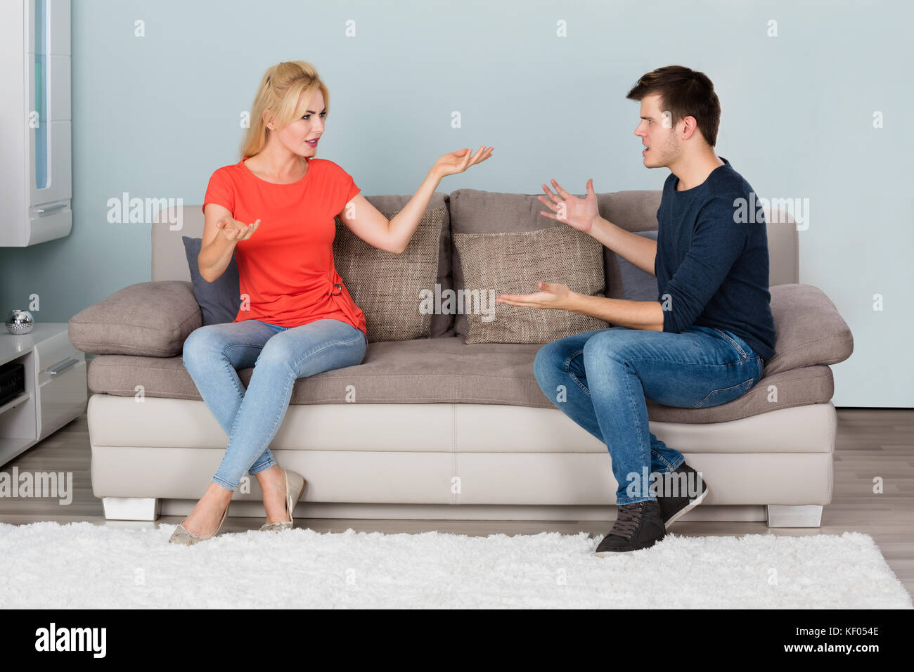 Sad Stressed Couple On Couch Quarreling About Infidelity With Each Other At Home - Stock Image